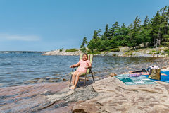 Stunning gorgeous view of child girl sitting and relaxing on rocky beach near the lake Royalty Free Stock Image