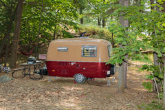 Stunning gorgeous view of old classic vintage camp trailer standing in woods. Great amazing inviting view of classic retro vintage camp trailer standing in woods Stock Photos