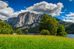 Stunning green field and alpine lake with mountains,Altaussee,Austria Stock Photography