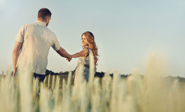 Stunning happy young couple in love posing in summer field holdi Royalty Free Stock Photos