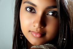 Stunning headshot of beautiful young black girl. Headshot of a stunning young black girl gazing gently into the camera. Model wearing subtle evening make up stock images