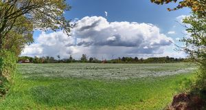 Stunning high resolution panorama of a northern german agricultural landscape on a sunny day with white cloud formations on a blue. Sky royalty free stock photography
