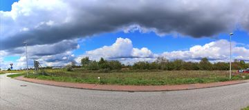 Stunning high resolution panorama of a northern german agricultural landscape on a sunny day with white cloud formations on a blue. Sky stock photos