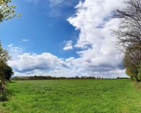 Stunning high resolution panorama of a northern german agricultural landscape on a sunny day with white cloud formations on a blue. Sky stock photo