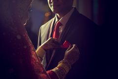 Stunning Indian bride looks at groom with passion while they stand in darkness Stock Image