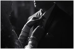 Stunning Indian bride looks at groom with passion while they stand in darkness Stock Photos