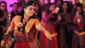 Stunning Indian bride in sari dances with guests