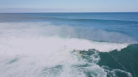 Stunning 4k aerial drone summer seascape of surfer surfing in huge white foamy waves in turquoise deep blue ocean water. Stunning aerial drone summer seascape of stock video footage
