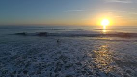Stunning 4k aerial drone view on warm sunrise over calm white foam ocean waves in Florida Satellite surf beach seascape stock video footage