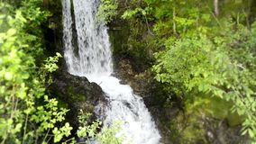 Stunning 4k steady wild nature landscape shot of small river waterfall running in green tree mountain cliff forest stock footage
