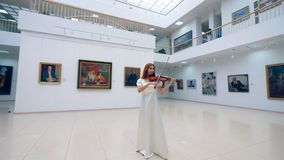 Stunning lady is playing the violin in the gallery. 4K stock footage