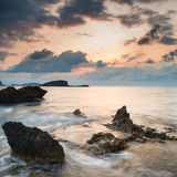Stunning landscape dawn sunrise with rocky coastline and long ex. Dawn sunrise landscape over beautiful rocky coastline in Mediterranean Sea Stock Photo
