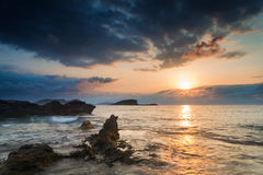 Stunning landscape dawn sunrise with rocky coastline and long ex Stock Photos