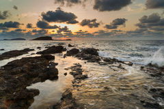Stunning landscape dawn sunrise with rocky coastline and long exp Royalty Free Stock Images