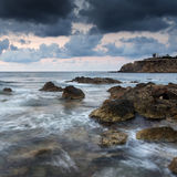 Stunning landscape dawn sunrise with rocky coastline and long exp Stock Photo