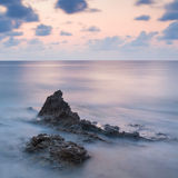 Stunning landscape dawn sunrise with rocky coastline and long exp Stock Photos
