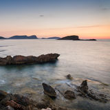 Stunning landscape dawn sunrise with rocky coastline and long exp. Dawn sunrise landscape over beautiful rocky coastline in Mediterranean Sea Stock Photos