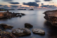 Stunning landscape dawn sunrise with rocky coastline and long exp. Dawn sunrise landscape over beautiful rocky coastline in Mediterranean Sea Stock Image