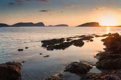 Stunning landscape dawn sunrise with rocky coastline and long exp Royalty Free Stock Photos