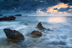 Stunning landscape dawn sunrise with rocky coastline and long exp. Dawn sunrise landscape over beautiful rocky coastline in Mediterranean Sea Stock Photo