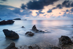Stunning landscape dawn sunrise with rocky coastline and long exp. Dawn sunrise landscape over beautiful rocky coastline in Mediterranean Sea Stock Photography