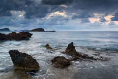 Stunning landscape dawn sunrise with rocky coastline and long exp Stock Image