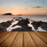 Stunning landscape dawn sunrise with rocky coastline and long exp. Dawn sunrise landscape over beautiful rocky coastline in Mediterranean Sea with wooden planks Royalty Free Stock Image