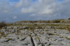 Stunning landscape of gray stones in burren. Stunning landscae of gray stones in burren with a cloudy blue sky Royalty Free Stock Photo