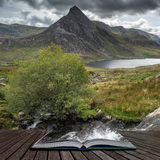 Stunning landscape image of countryside around Llyn Ogwen in Snowdonia during early Autumn coming out of pages of open story book stock image