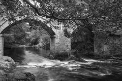 Stunning landscape image of old stone bridge over flowing river. Beautiful landscape image of old stone bridge over flowing river in Autumn in blakc and white royalty free stock images