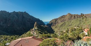Stunning landscape mountain village in deep canyon with jungle forest on a paradise island. Beautiful golden hour of warm sunny stock photography