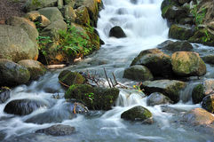 Stunning landscape of a small waterfall cascading Stock Images