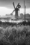 Stunning landscape of windmill and river at dawn in black and wh Royalty Free Stock Photo