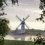 Stunning landscape of windmill and river at dawn on Summer morni Stock Photo