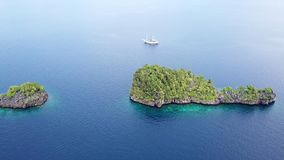 Aerial of Ship and Tropical Islands in Raja Ampat. The stunning limestone islands found in Raja Ampat are surrounded by healthy coral reefs. This beautiful stock video