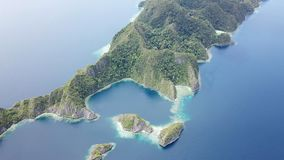 Aerial of Tropical, Limestone Islands in Raja Ampat. The stunning limestone islands found in Raja Ampat are surrounded by healthy coral reefs. This beautiful stock video footage