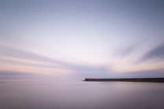 Stunning long exposure landscape lighthouse at sunset with calm Stock Photo
