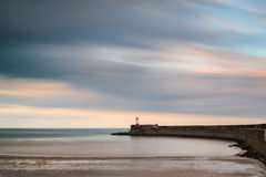 Stunning long exposure landscape lighthouse at sunset with calm Stock Images