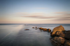 Stunning long exposure landscape of sea over rocks at sunset Stock Photos