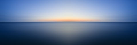Stunning long exposure seascape image of calm ocean at sunset Stock Photos