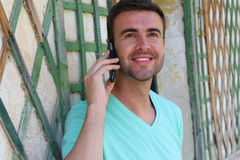Stunning male calling by phone during summer vacation.  Royalty Free Stock Photography