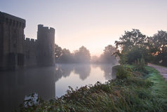 Stunning moat and castle in Autumn Fall sunrise. Beautiful medieval castle and moat at sunrise with mist over moat and sunlight behind castle Royalty Free Stock Images
