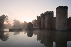 Stunning moat and castle in Autumn Fall sunrise. Beautiful medieval castle and moat at sunrise with mist over moat and sunlight behind castle Royalty Free Stock Photo
