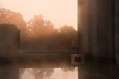 Stunning moat and castle in Autumn Fall sunrise. Beautiful medieval castle and moat at sunrise with mist over moat and sunlight behind castle Royalty Free Stock Image