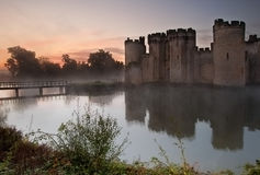 Stunning moat and castle in Autumn Fall sunrise with mist. Beautiful medieval castle and moat at sunrise with mist over moat and sunlight behind castle Royalty Free Stock Photography
