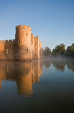 Stunning moat and castle in Autumn Fall sunrise with mist. Beautiful medieval castle and moat at sunrise with mist over moat and sunlight behind castle Royalty Free Stock Images