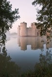 Stunning moat and castle in Autumn Fall sunrise with mist over m. Beautiful medieval castle and moat at sunrise with mist over moat and sunlight behind castle Stock Photos