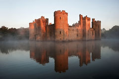 Stunning moat and castle in Autumn Fall sunrise with mist over m. Beautiful medieval castle and moat at sunrise with mist over moat and sunlight behind castle Stock Image