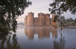 Stunning moat and castle in Autumn Fall sunrise with mist over m. Beautiful medieval castle and moat at sunrise with mist over moat and sunlight behind castle Royalty Free Stock Image
