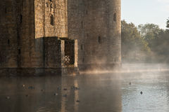 Stunning moat and castle in Autumn Fall sunrise with mist over m. Beautiful medieval castle and moat at sunrise with mist over moat and sunlight behind castle Royalty Free Stock Photos